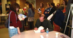 Professor and author Gary Schmidt signs a book at the Mazza conference.  Photo by Anna Lambers