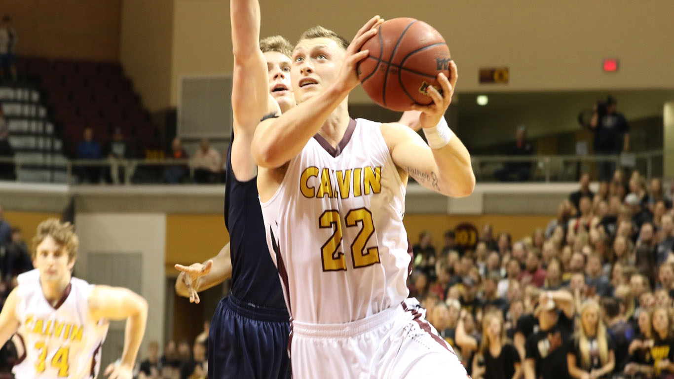 Number 22 Cam Denney drives the ball, he recorded a double-double, tallying 15 points and 17 rebounds. Photo courtesy Calvin Sports Information