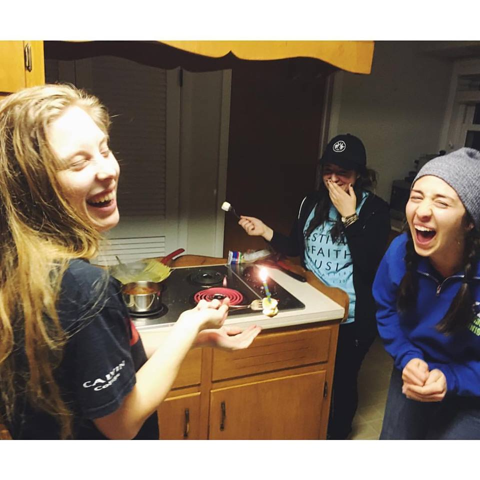 Maaike Mudde, Kendra Larsen and Kaitlyn Farris laugh as they roast marshmallows over a burner. Photo credit  Suzanne Melin.