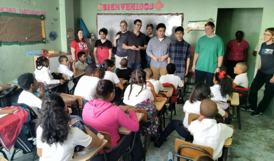 The+CS+interim+class+visits+a+classroom+in+the+Dominican+Republic+to+give+instruction+on+how+to+use+devices+they+are+delivering+to+the+school.+
