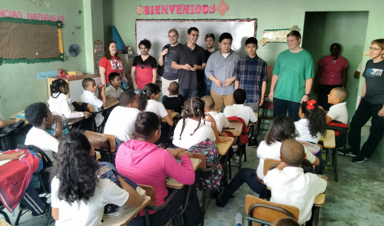 The CS interim class visits a classroom in the Dominican Republic to give instruction on how to use devices they are delivering to the school.