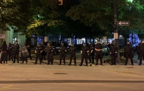Grand Rapids police clad in riot gear defend a street entrance during a night of protests and rioting on May 30