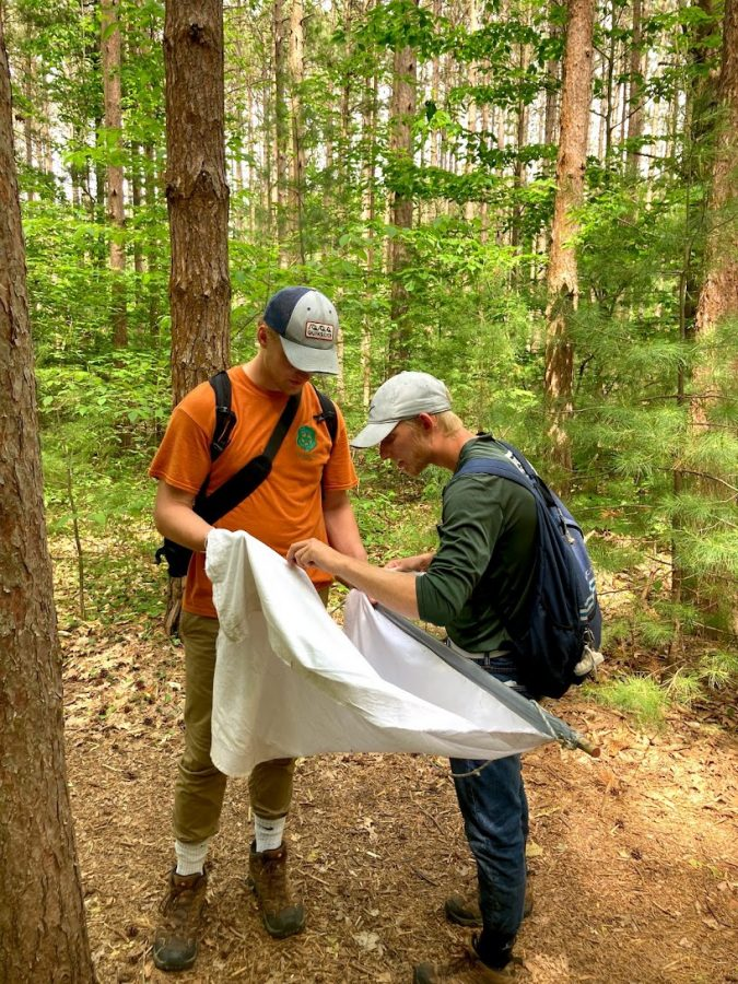 Andre Kapteyn (left) and Andrew Vander Tuig (right) collect a tick.