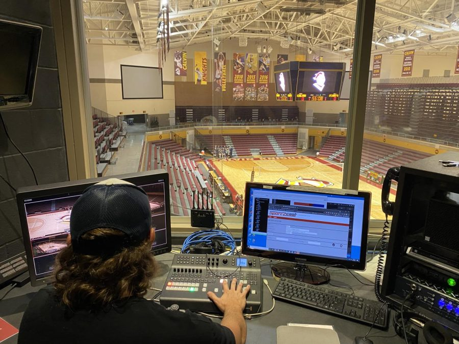 Calvin junior Joe Hayduk looks out over Van Noord Arena from the tech booth before a volleyball game.