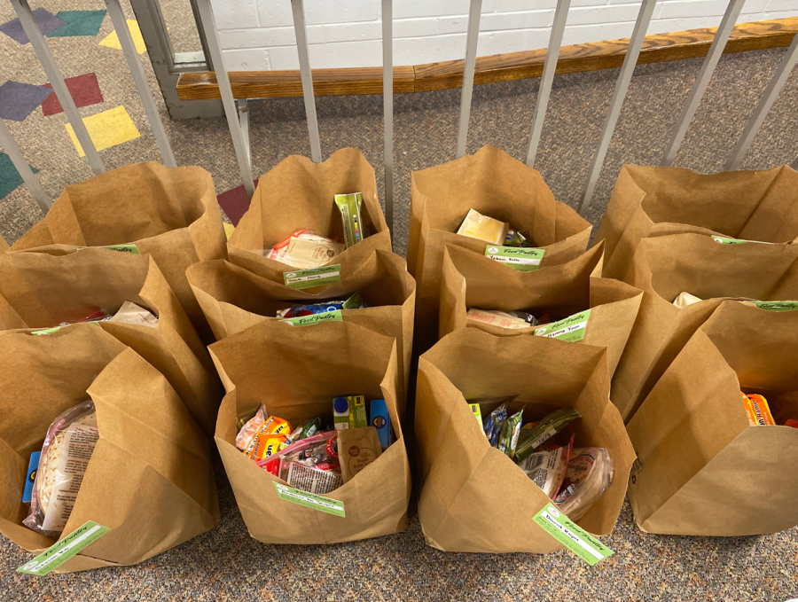 Food bags can include milk, bread, and other staple food items.